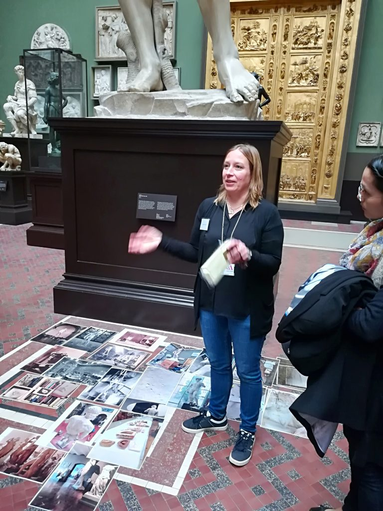 Photograph of a V&A conservator standing in front of a plaster cast in the Cast Courts, describing her work (c) Sally Foster