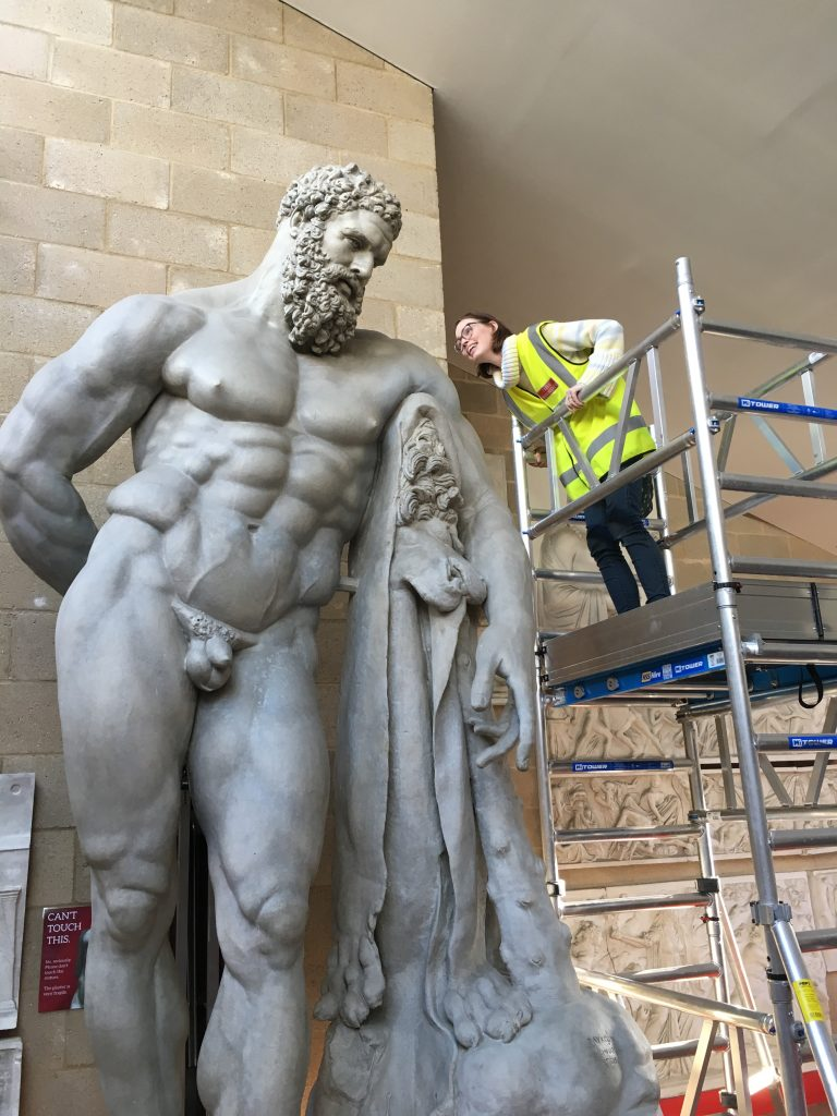 Dr Susanne Turner inspecting a large plaster cast of the Farnese Hercules (c) Museum of Classical Archaeology, University of Cambridge