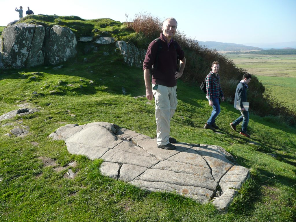 Visitors engage with replica lying over carved bedrock at Dunadd, Scotand (c) Sally Foster
