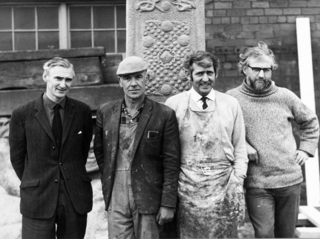 Proud engineer, artists and craftsmen standing by recently made concrete replica of St John's Cross, Iona. Photographer Arthur Macgregor, (c) courtesy of Historic Environment Scotland (J R Scott Collection)