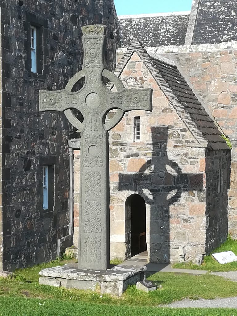 The 1970 replica of the St John's Cross, Iona, casts a shadow on the 1955/6 reconstruction of the burial place of St Columba (c) Sally Foster